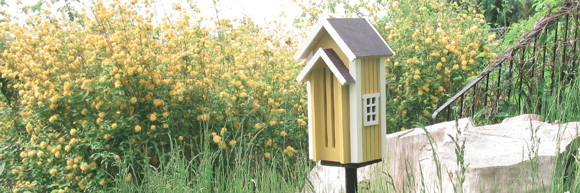A yellow butterfly house in a flower garden