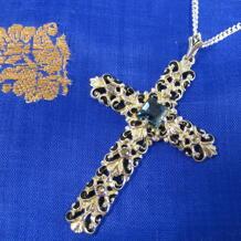 Kors i förgyllt silver,svart emalj och akvamarin.