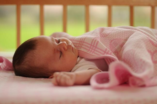 Babyfilt stickad med barnets namn, födelsedatum, vikt och längd.