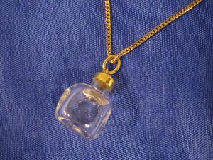 Hängsmycke i 18 karat guld. Glasflaska med guldfäste.