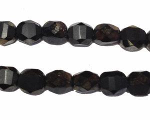 Fasetterad matt svart pärla med guldkanter, 6 mm. En sträng.