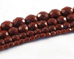 Djupt röda fasetterade pärlor i snakecoating, 8 mm. Ca 16 cm sträng.