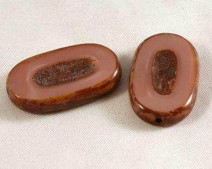 Oval tjeckisk fire polish pärla i smutsrosa med terrakottabrunt, 25*10 mm. 2 stycken.