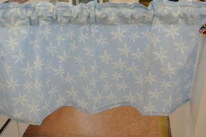 ljusblå gardinkappa med vita blommor