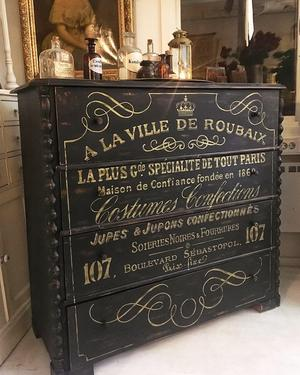 Svart chiffonjé med fransk text i guld