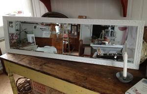 Hög och smal spegel med ornamenterad ram och fasettslipat glas